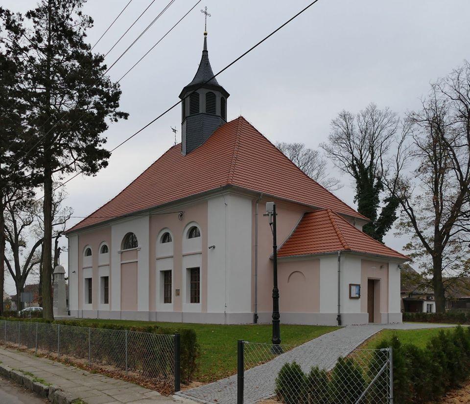 Zdjęcie przedstawia Kościół pw.Tadeusza Judy w Kurzniach ( budynek o biało-różowych ścianach, czerwonym szpiczastym dachem i wieżą)