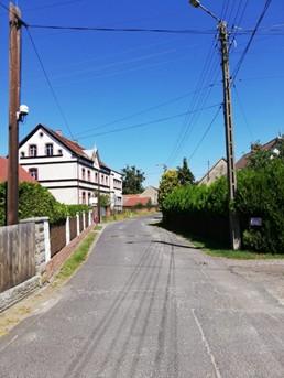 Zdjęcie poglądowe przedstawiające ulicę Klasztorną w Popielowie W tle widać biały budynek mieszkalny otoczony płotem i bujną roślinością. Obok znajduje się asfaltowa uliczka. Po prawej stronie znajdują się wysokie krzewy